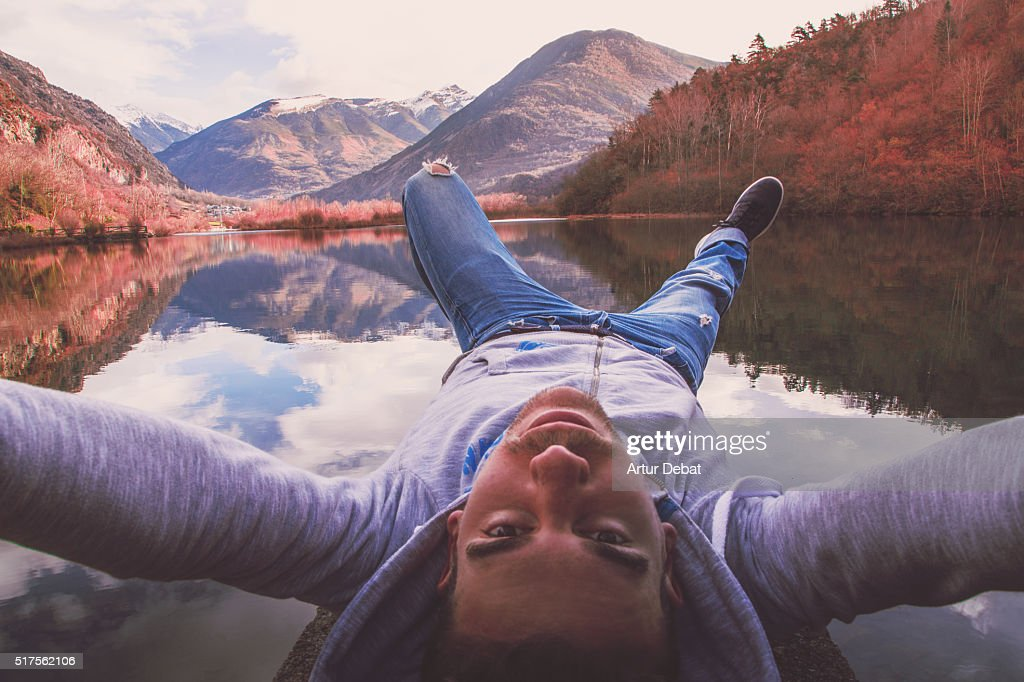 Man taking a selfie with the beautiful water reflection on the lake from the dock with the beautiful mountain landscape of the Catalan Pyrenees in a road trip. : Stock Photo