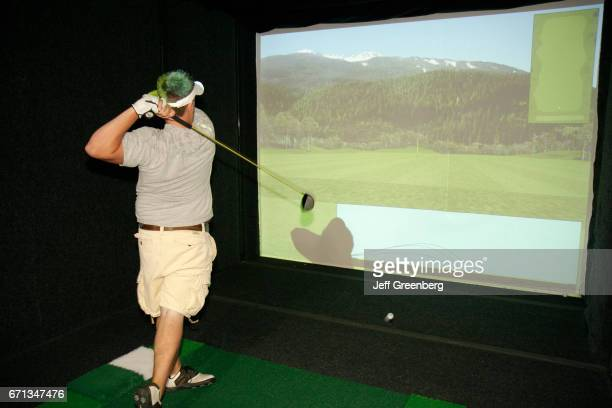 A man taking a swing on a golf simulator at Creekside Golf Course and Training Center