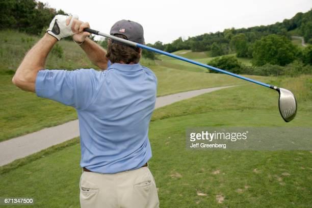 A man taking a swing on the golf course at Leelanau Club