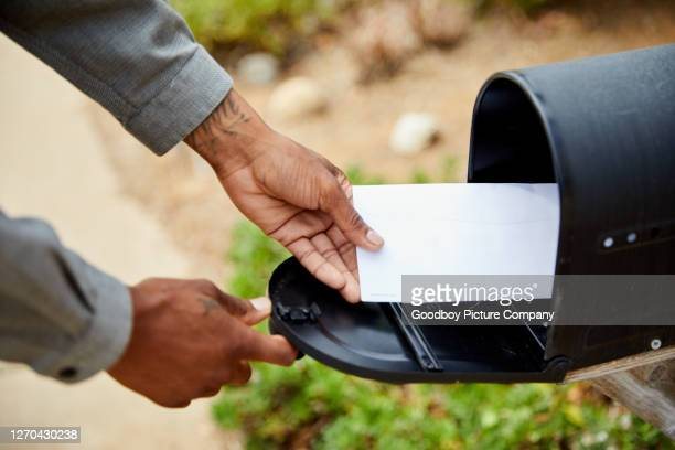 man taking an envelope out of his mailbox - domestic mailbox stock pictures, royalty-free photos & images