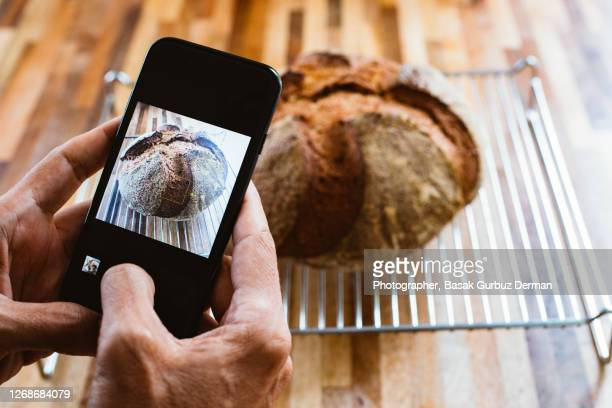 a man taking and sharing the photo of an homemade sourdough bread with mobile / smart phone - baking bread stock pictures, royalty-free photos & images