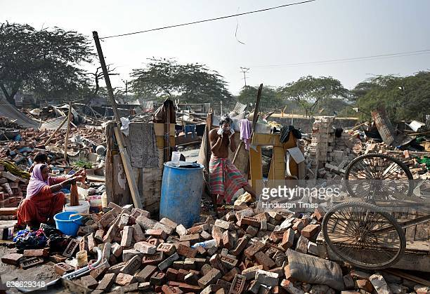 A man taking bath as a woman washes cloths in a house demolished in joint drive of MCD and DDA at Kishangarh on December 8 2016 in New Delhi India A...