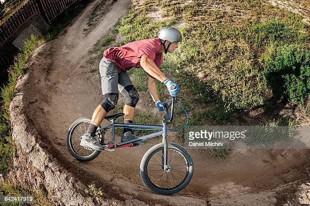 man taking berm turn on bmx bike - bmx cycling stock pictures, royalty-free photos & images