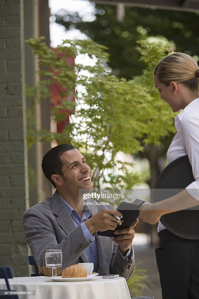 Man taking bill from waitress at outdoor cafe : Foto stock