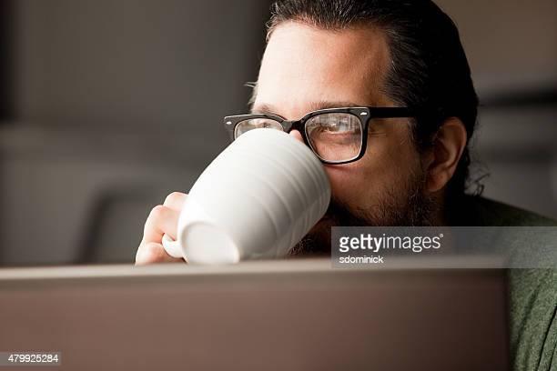 Homme prenant une pause pour boire un café pour ordinateur portable