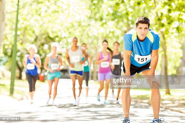 Man Taking Break While Competitors Running Marathon