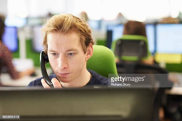 man taking call in call centre - richard drury stock pictures, royalty-free photos & images