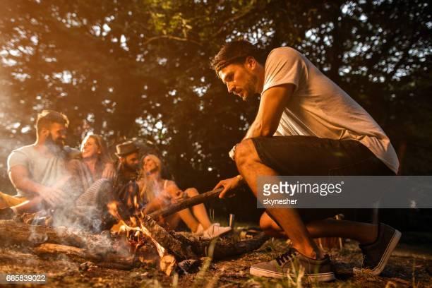 Der Mensch kümmert sich Kaminfeuer beim camping mit Freunden.