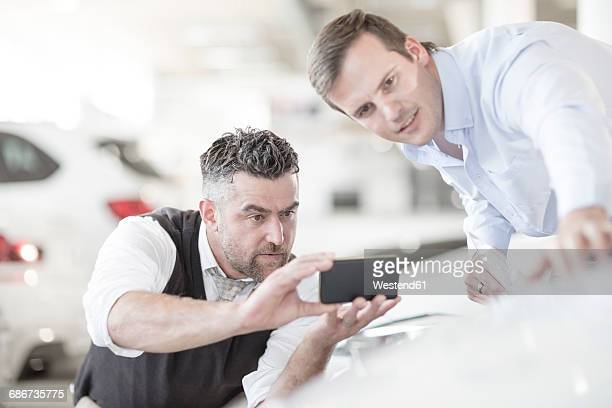 Man taking cell phone picture at car dealership