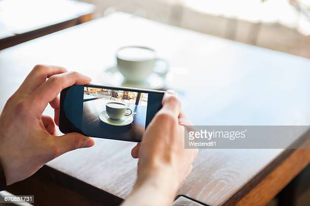 man taking cell phone picture of cup of coffee - capturing an image stock photos and pictures