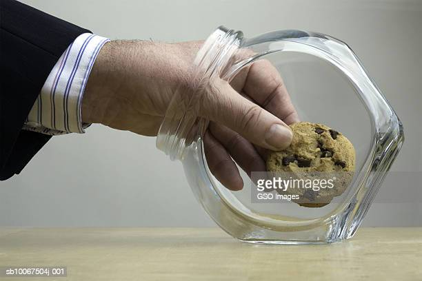 Man taking cookie from cookie jar, close-up of hand