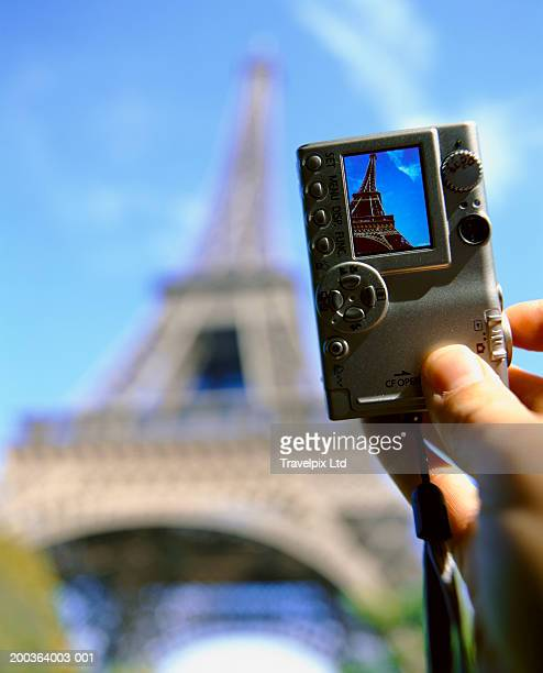 Man taking digital photo of Eiffel Tower, close-up
