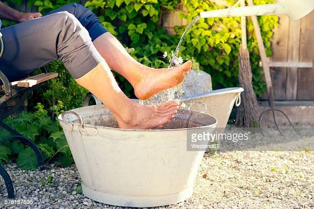man taking footbath in a garden - erfrischung stock-fotos und bilder