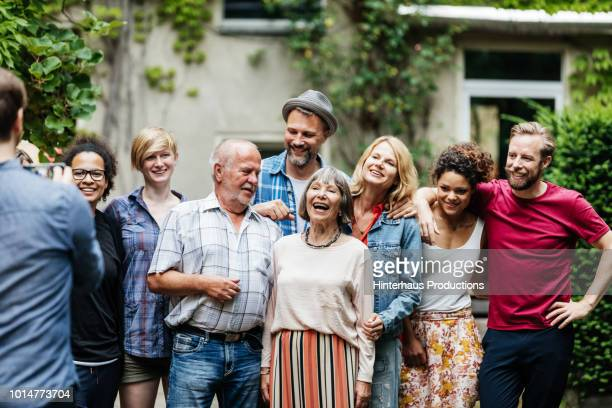 man taking group photo of family at bbq - sociale bijeenkomst stockfoto's en -beelden