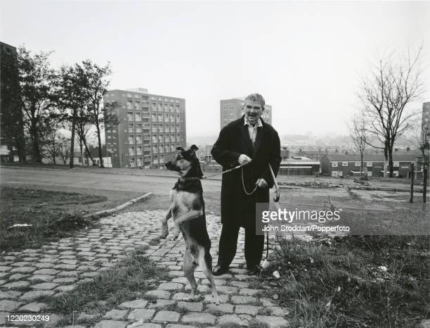 Man taking his dog for a walk in Liverpool, circa 1982. The 1980s saw the City of Liverpool's fortunes sink to their lowest postwar point. Although...