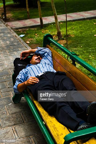 Man taking his post-lunch nap on a bench, in a park of central Tehran.
