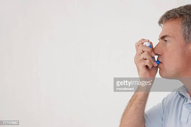 Man Taking Inhaler