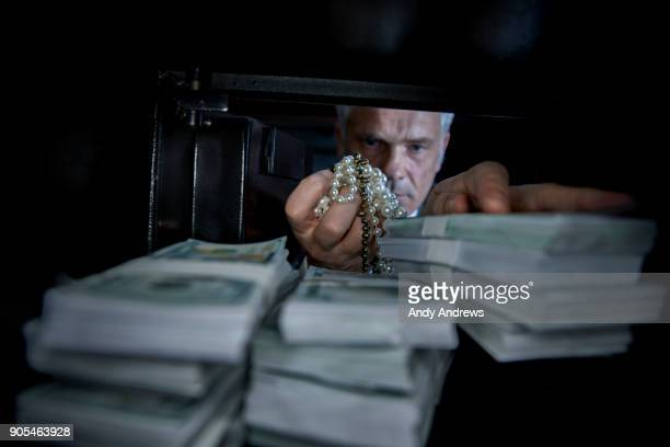 POV Man taking jewellery out of a safe