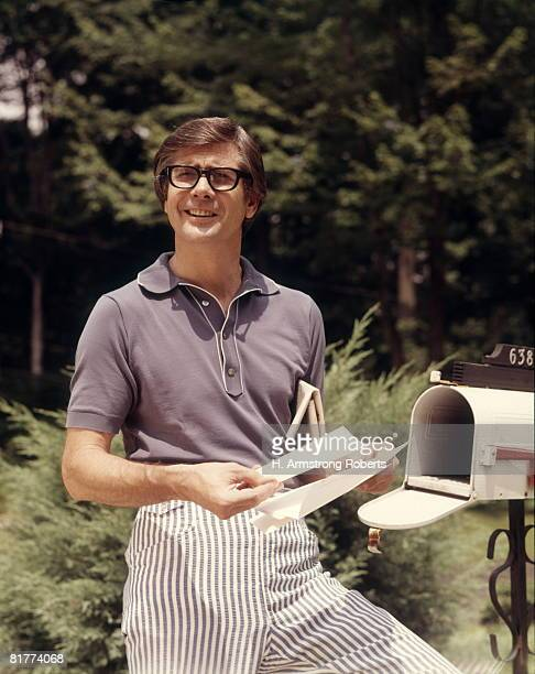 man taking mail from rural mail box. - domestic mailbox stock pictures, royalty-free photos & images