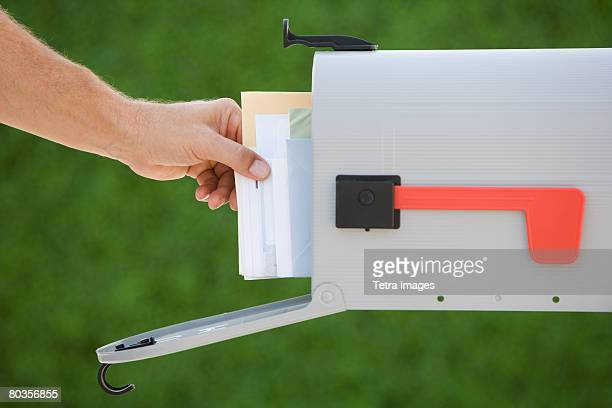 man taking mail out of mailbox - domestic mailbox stock pictures, royalty-free photos & images