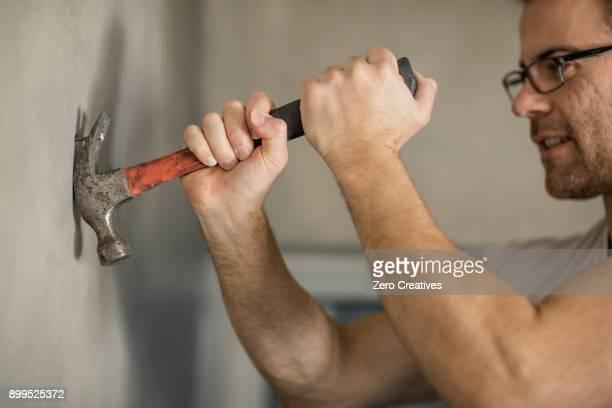 Man taking nail from wall, using hammer