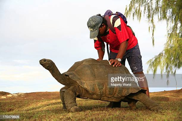 Man taking notes for species research on Aldabra Island in Seychelles. Aldabra is the world's largest coral atoll, in the Aldabra Group of islands in...