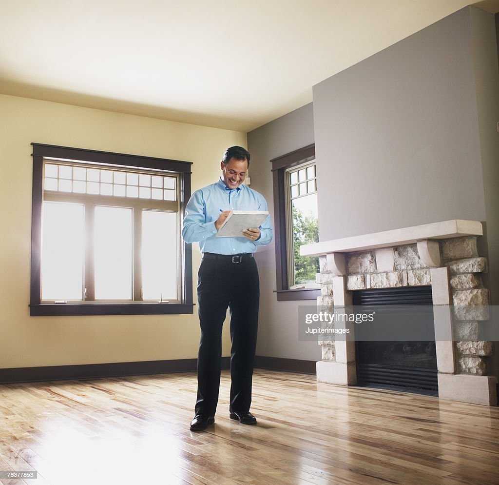 Man taking notes in empty house : Stock Photo