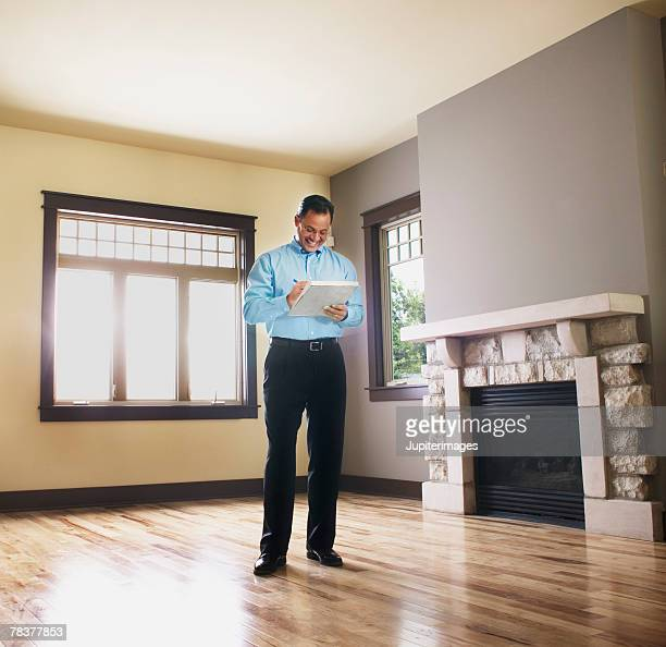 man taking notes in empty house - inspector stock pictures, royalty-free photos & images