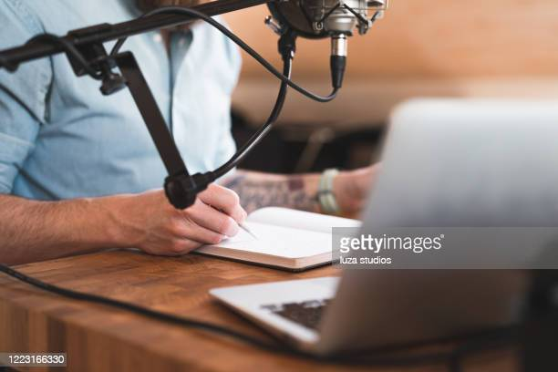 man taking notes while recording a podcast - makeshift stock pictures, royalty-free photos & images