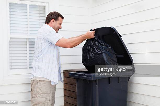 man taking out garbage - garbage bin stock pictures, royalty-free photos & images
