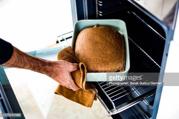 a man taking out the cooked bread / cake from the oven - baking bread stock pictures, royalty-free photos & images