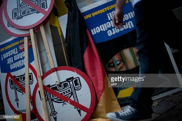 A man taking part in a rally of the farright group Pro Deutschland near the AsSahaba mosque in Berlin's Wedding district walks past banners of with...