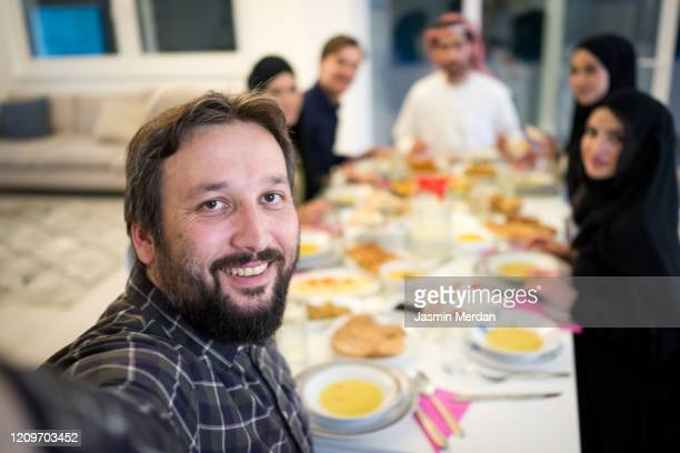 man taking phone selfie during having dinner with friends - iftar stock pictures, royalty-free photos & images