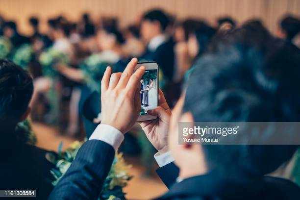 man taking photo at the wedding - photo messaging stock photos and pictures