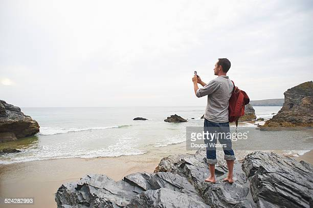 Man taking photo of beach with smart phone.