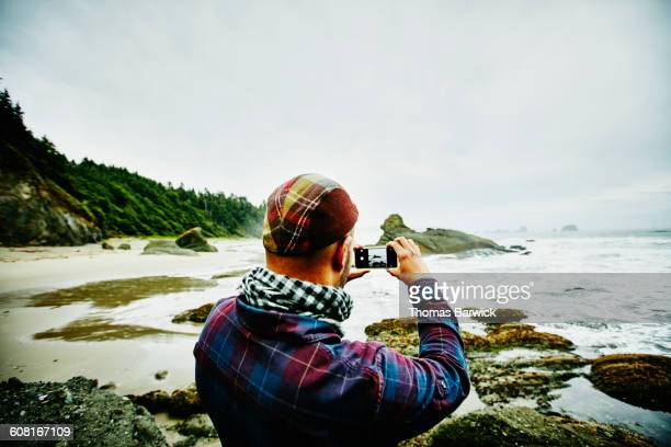 Man taking photo of beach with smartphone