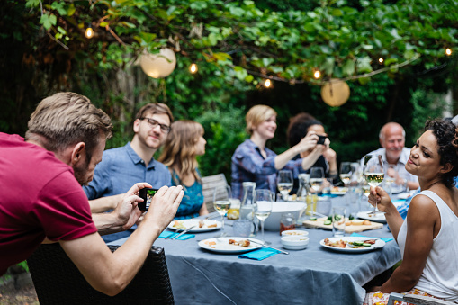Man Taking Photo Of Friends At Family BBQ - gettyimageskorea