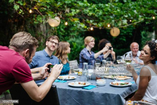 man taking photo of friends at family bbq - outdoor party stock pictures, royalty-free photos & images