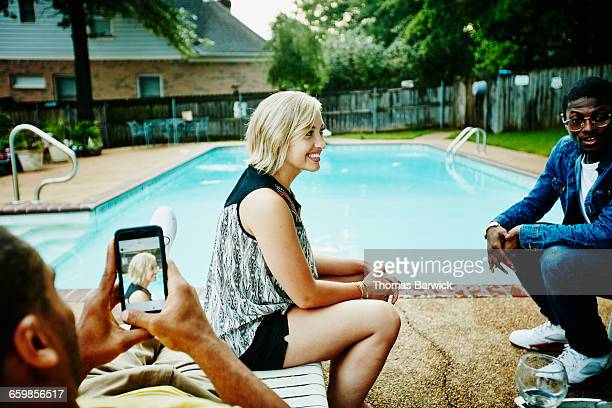 Man taking photo of friends hanging out by pool