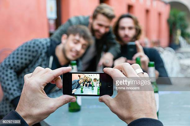 Man taking photo of friends with mobile phone