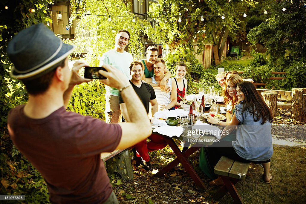 Man taking photo of friends with smart phone : Stock Photo