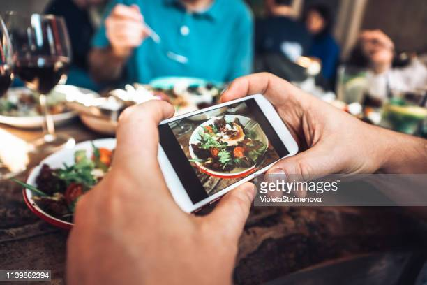 man taking photo of healthy food with smartphone - photo messaging stock pictures, royalty-free photos & images