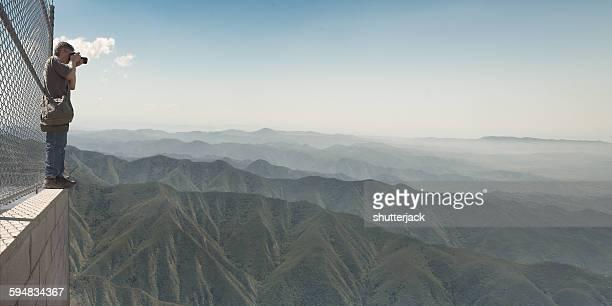Man taking photo of mountain range