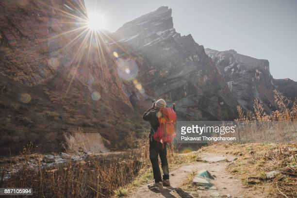 annapurna, nepal - november 24, 2017: man taking photo of nature - annapurna conservation area stock photos and pictures