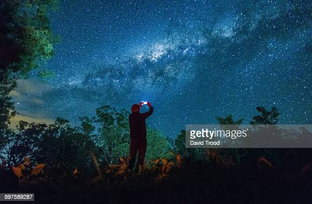 Man taking photo of night sky with smart phone