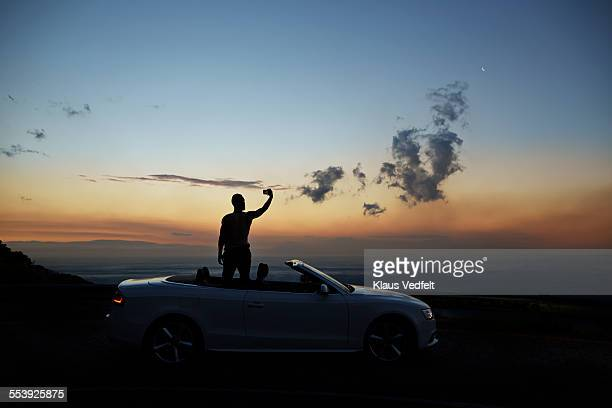 Man taking photo of sunset, standing in open car