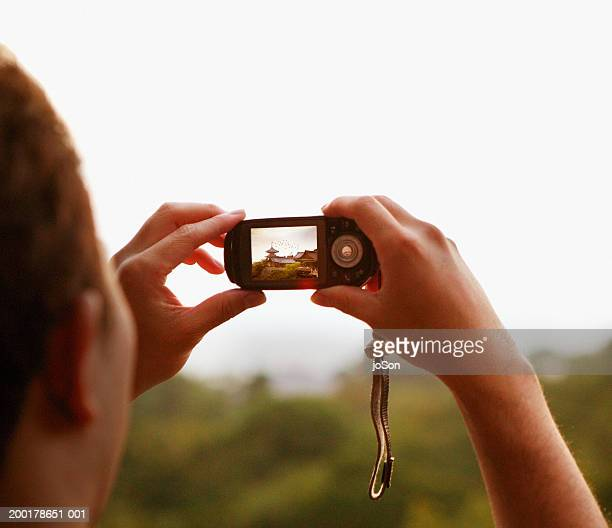 man taking photo of temple with camera phone, view over shoulder - travel14 stock pictures, royalty-free photos & images
