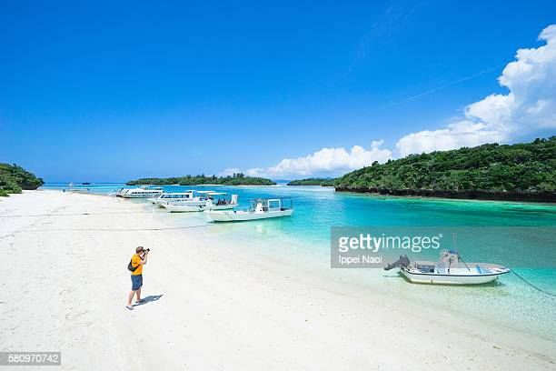 Man taking photo of tropical lagoon beach, Kabira Bay, Okinawa