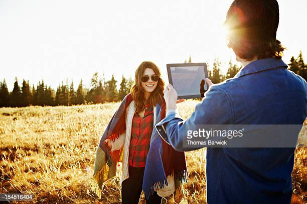 Man taking photo  of woman with digital tablet