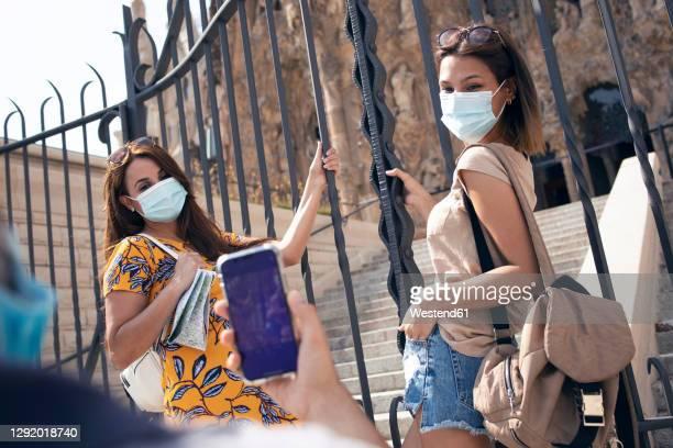 man taking photo of women wearing face mask standing by gate against sagrada familia at barcelona, catalonia, spain - familia stock-fotos und bilder